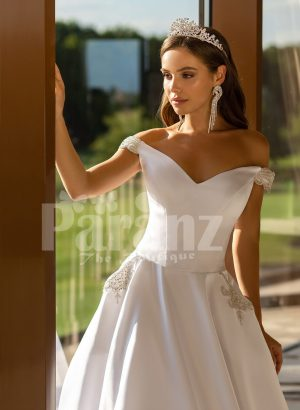 Beautiful metal white off-shoulder tulle underneath Cinderella wedding gown close view