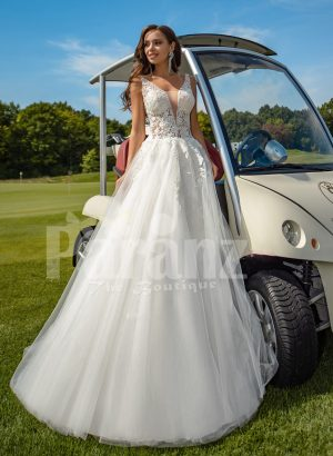 Flared and long tulle pearl white wedding gown with lacy bodice
