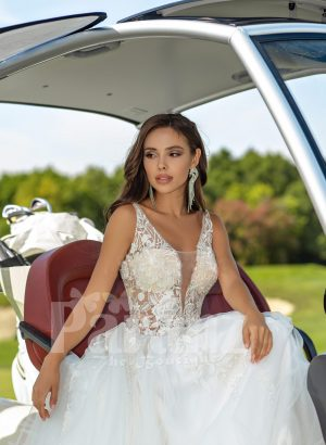 Flared and long tulle pearl white wedding gown with lacy bodice close view
