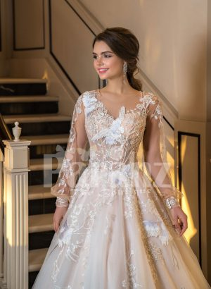 Full Arabian styled sleeve flared tulle wedding gown with flower appliquéd bodice close view