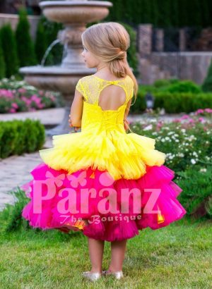 Contrast bright yellow-pink tea length baby party dress with ruffle skirt and floral bodice back side view