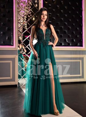 Womans stylish deep green evening gown with side slit tulle skirt and rich rhinestone bodice