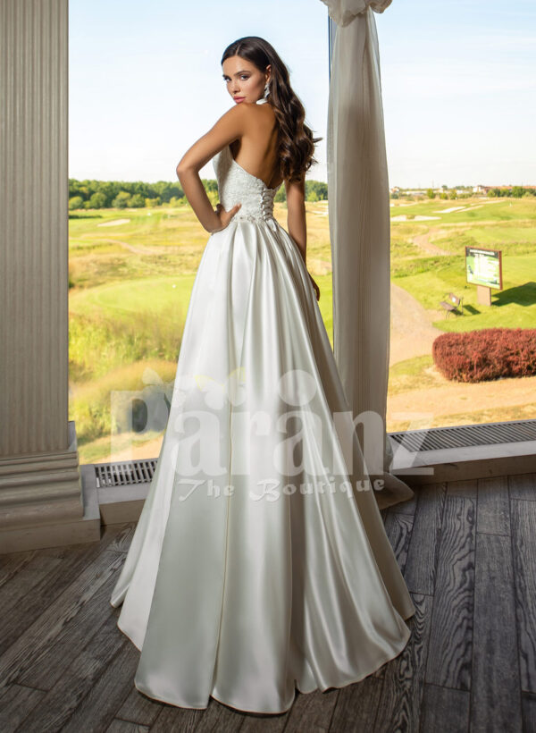 Closed neck and open back flared satin wedding gown with tulle skirt underneath back side view