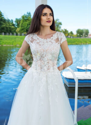 Elegant pearl white floor length flared tulle skirt wedding gown with lacy bodice close view