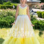 Light yellow sleeveless baby gown with rhinestone neckline and floor length tulle skirt
