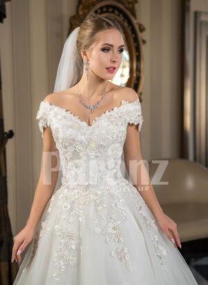 Pearl white cap sleeve floor length tulle wedding gown with floral bodice Close view