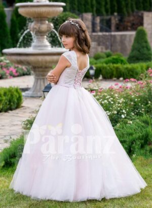 Small cap sleeve soft and lightweight light pink baby gown with flared tulle skirt side view