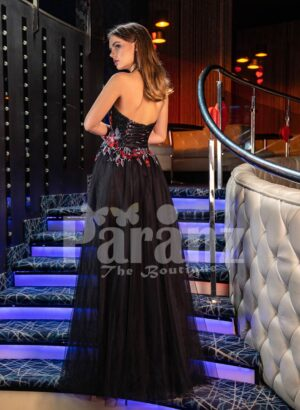 Women's beautiful off-shoulder black tulle skirt gown with colorful floral appliquéd bodice back side view