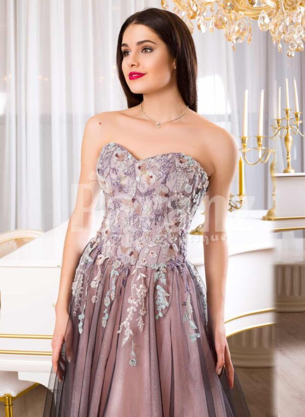 Women's elegant off-shoulder evening gown with long tulle skirt and rich appliquéd bodice