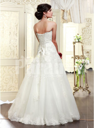 Women's elegant off-shoulder style wedding gown with flared and high volume tulle skirt back side view