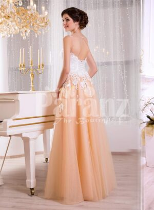 Women's glam evening gown with peachy orange flared tulle skirt and appliquéd white bodice side view