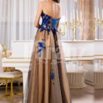 Women's off-shoulder long tulle evening gown with bright blue floral appliquéd bodice back side view