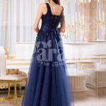 Women's sleeveless navy floor length gown with rich rhinestone studded bodice back side view