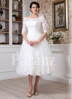 Women's tea length white lacy bodice and tulle skirt wedding gown