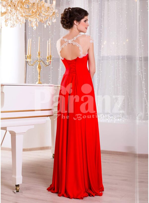 Women's vibrant red sleeveless evening gown with sleek and long floor length tulle skirt side view